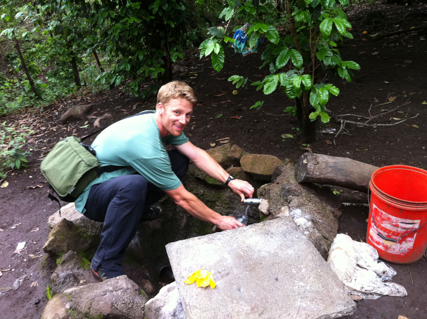 Josiah fills up his bottle from the tap of one of the rainwater harvesting tanks