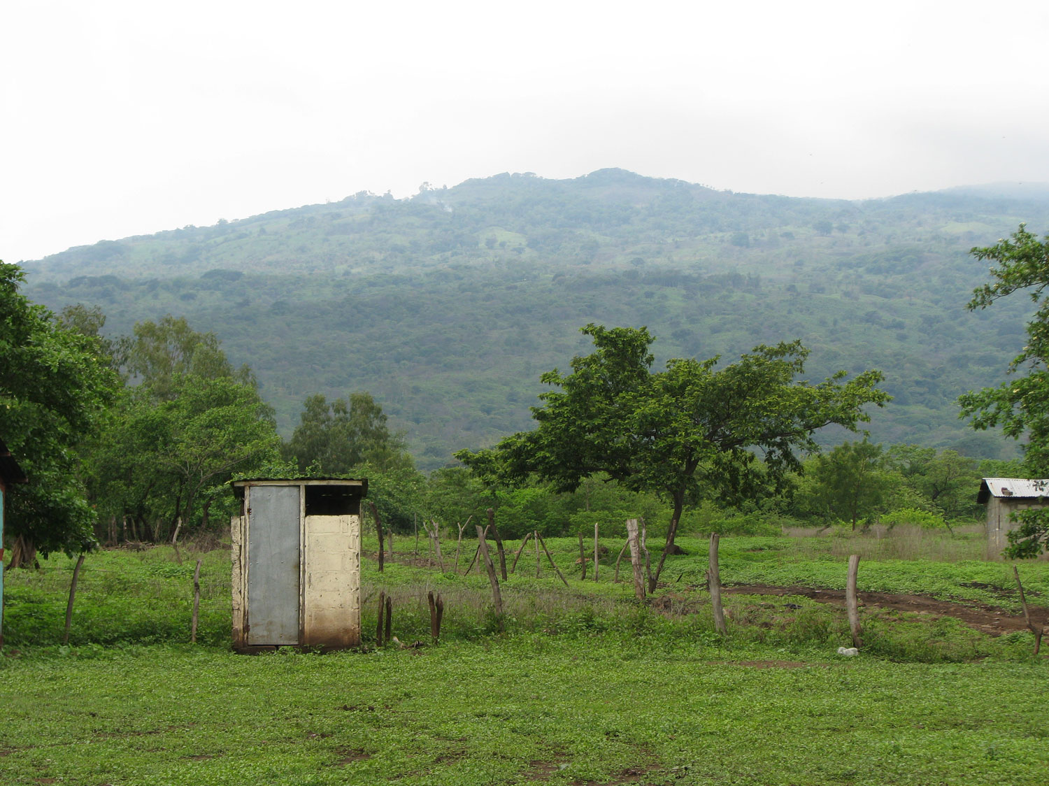 A latrine with the hill containing the hillside community of El Ojochal visible in the background. Today we will hike up to this community.