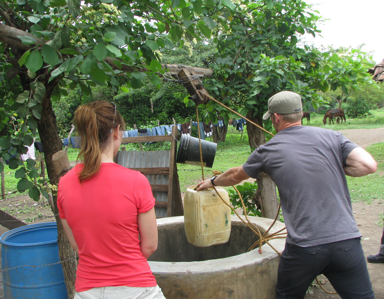 Kirstin watches as Josiah brings up water from a hand dug well.