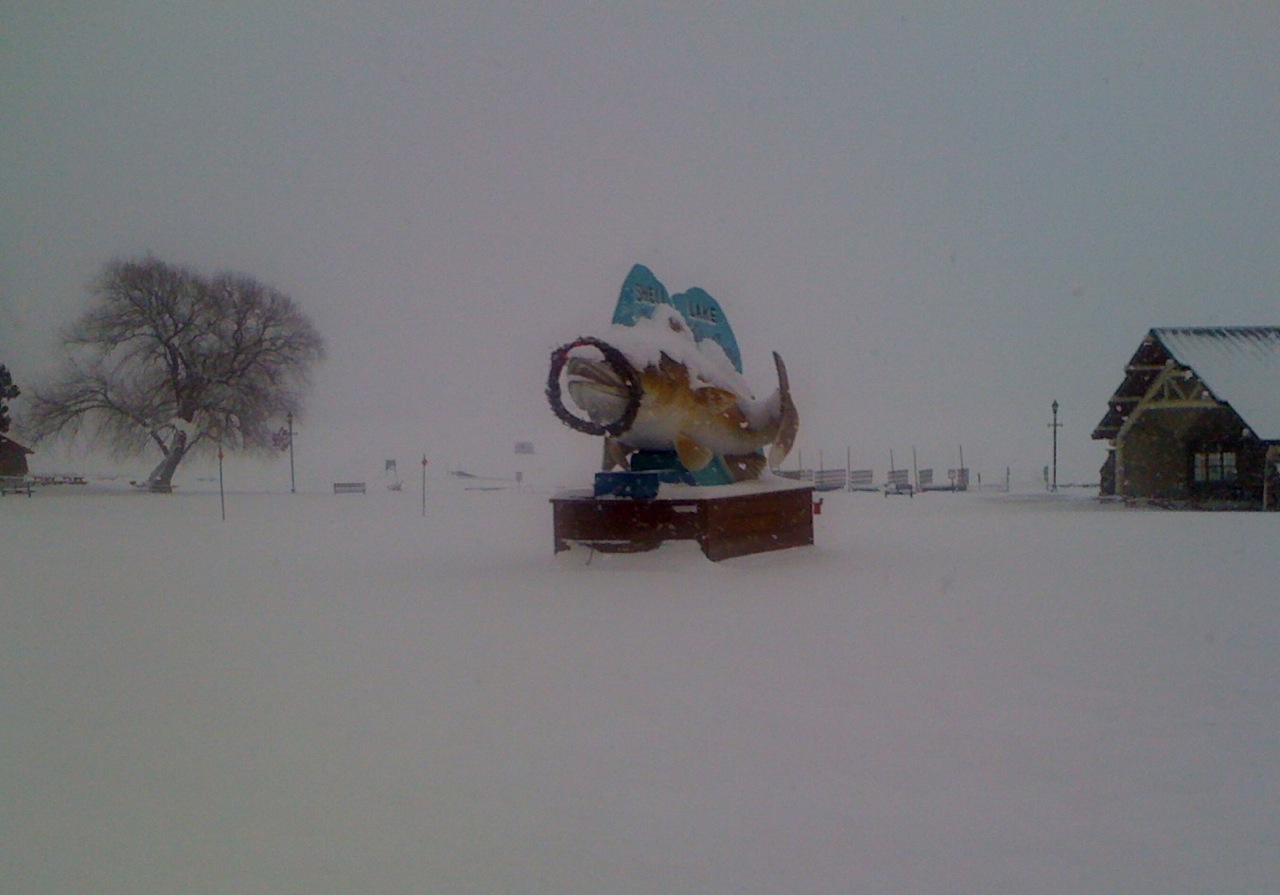 The shell lake mascot (and an ice fishing hut in the background on the lake)